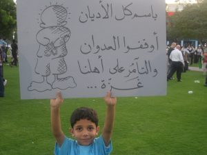 "Sign reads: ""In the name of all religions, please stop attacking, and conspiring against our families in Gaza"""
