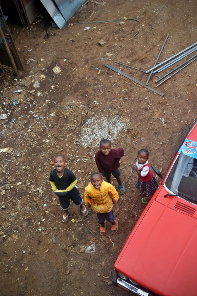 Four children standing next to a car, viewed from above.