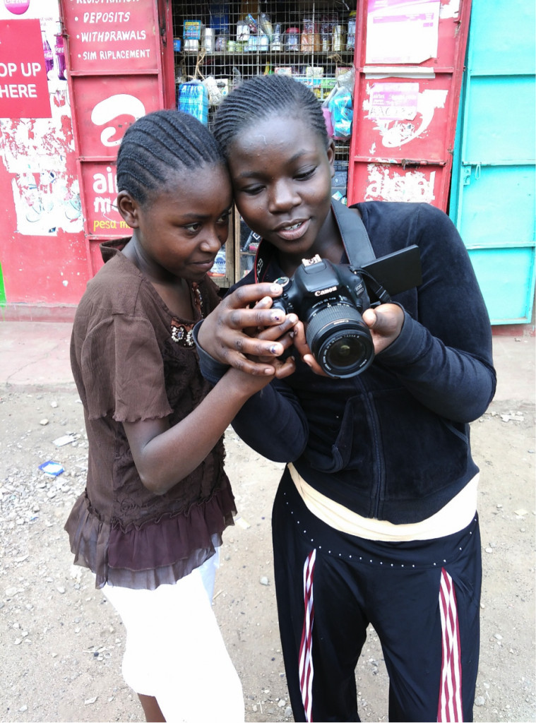 Two girls leaning excitedly over a camera.