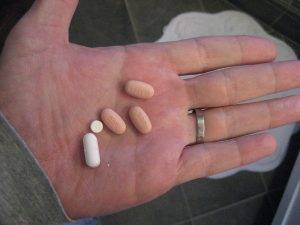 An outstretched hand with vicodin and other medications.