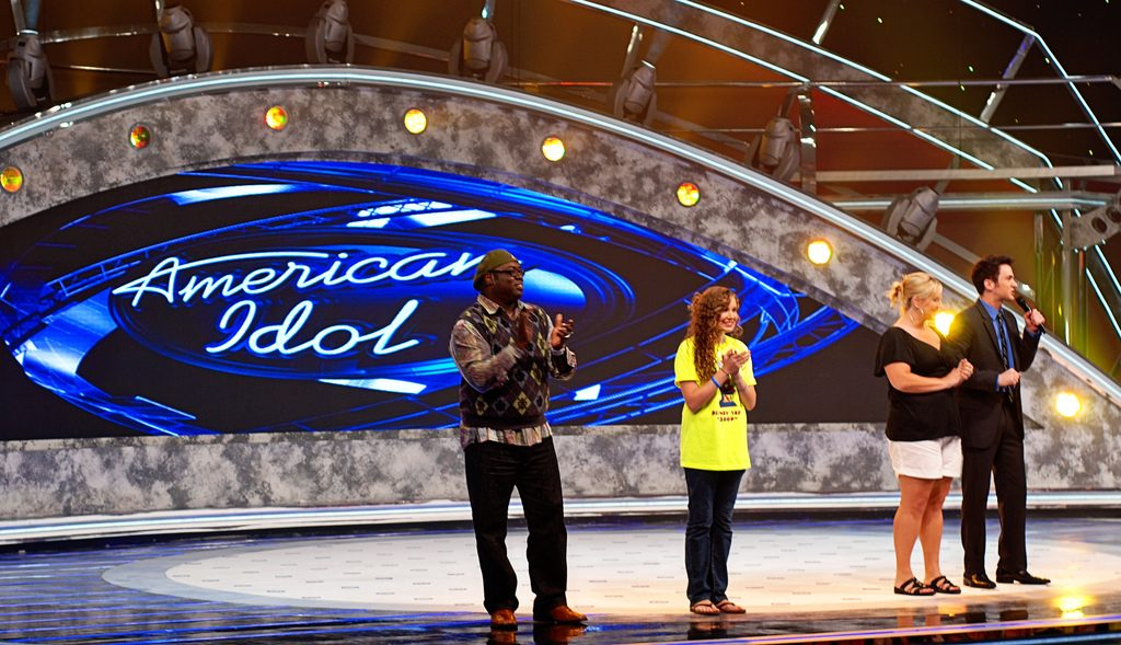 Performers singing on an American Idol stage.
