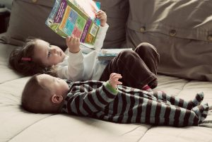 Two babies sprawled on a bed with a picture book.