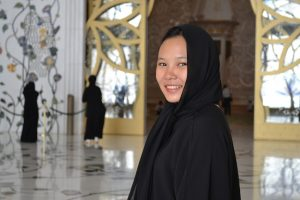 A smiling woman wearing an abaya.