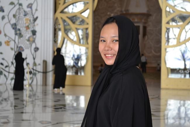 A smiling woman wearing an abaya.