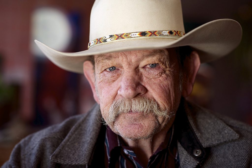 A older man wearing a cowboy hat and squinting at the camera.