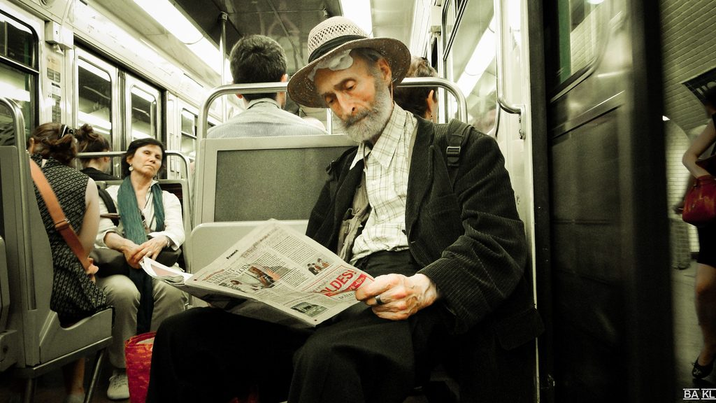 A man reading the newspaper on the subway.