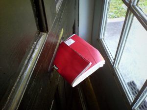 A Netflix envelope wedged in a mail slot.