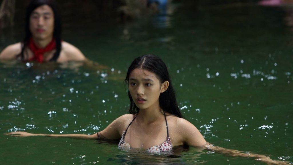 Two people splashing in the water in a still from the Chinese film Mei Ren Yu or The Mermaid.