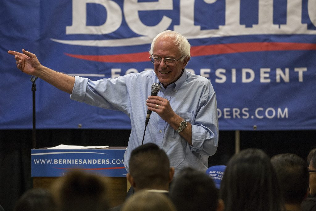 Bernie Sanders speaks in front of a crowd of enthusiastic supporters.