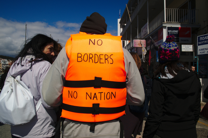 A person wearing a life jacket that reads NO BORDERS NO NATION