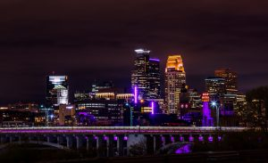 The skyline in Minneapolis, with buildings and bridges illuminated in purple.