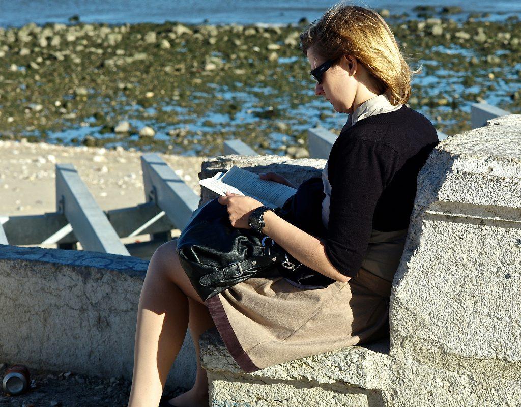 A woman reading on the seashore.