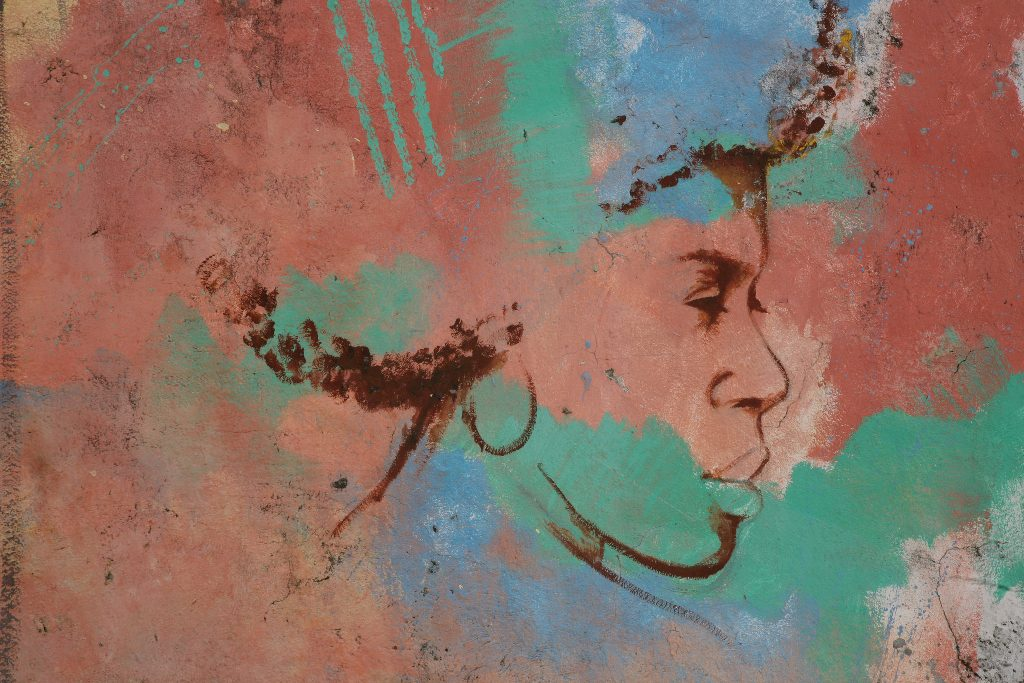 Graffiti of a woman with full lips, hoop earrings, and a large afro on the wall of a building.