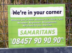 A sign at a train platform encouraging people to call the Samaritans rather than commit suicide.