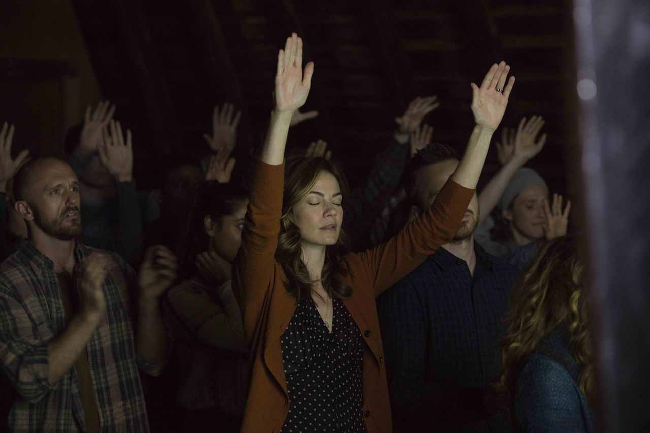 Worshipers raising their hands at a cult meeting in THE PATH