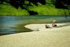 A person reading a book on the bank of a river.