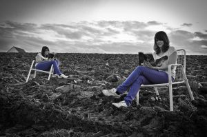 Two people reading books in the middle of a field.