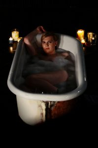 A still from CHASING BLUE, featuring a person lying in a bathtub.