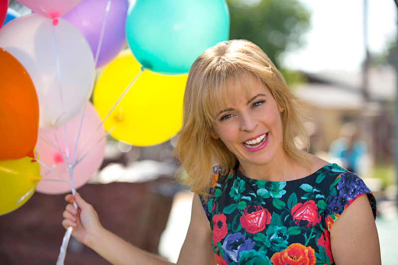 A still from Lady Dynamite, featuring a light-skinned person with blonde hair holding a bunch of balloons.