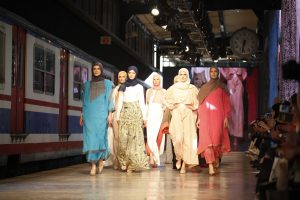 Women in hijab strutting down a runway.