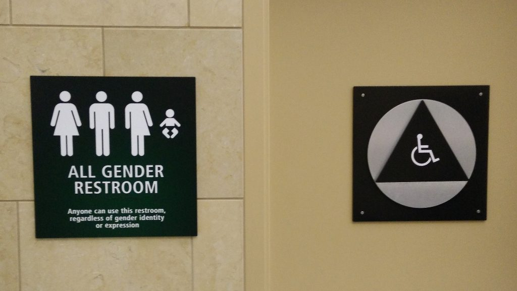 A bathroom sign indicating that a restroom is available for people of all genders, along with parents and disabled people.