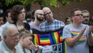 A gay couple leans on each other while listening to a speaker at a vigil for victims of the Pulse shooting.