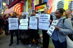 Attendees of a London vigil for Orlando's shooting victims holding up solidarity placards.