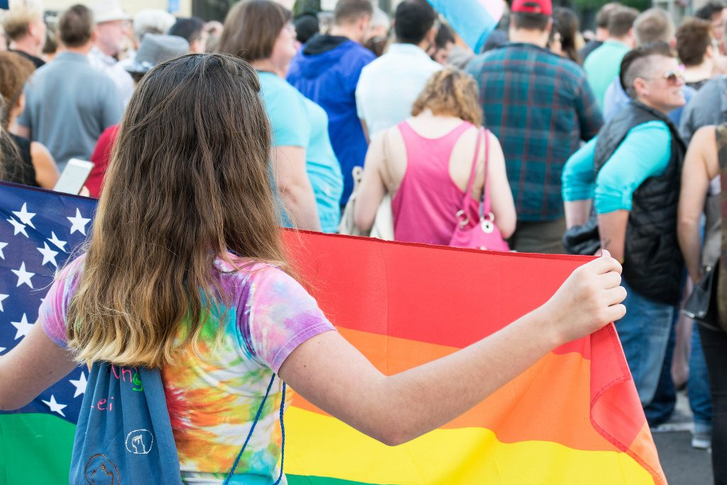 A young girl in tie-dye carrying a rainbow flag.