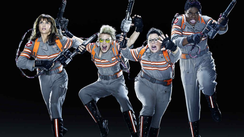 The four women of Ghostbusters, jumping in the air.