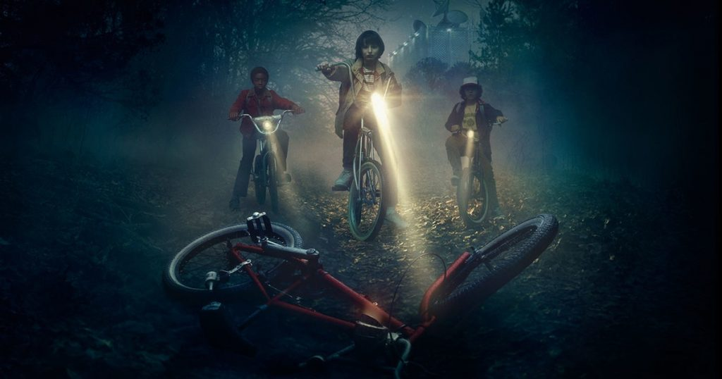 Children shining their bike lights on an abandoned bicycle in Stranger Things.