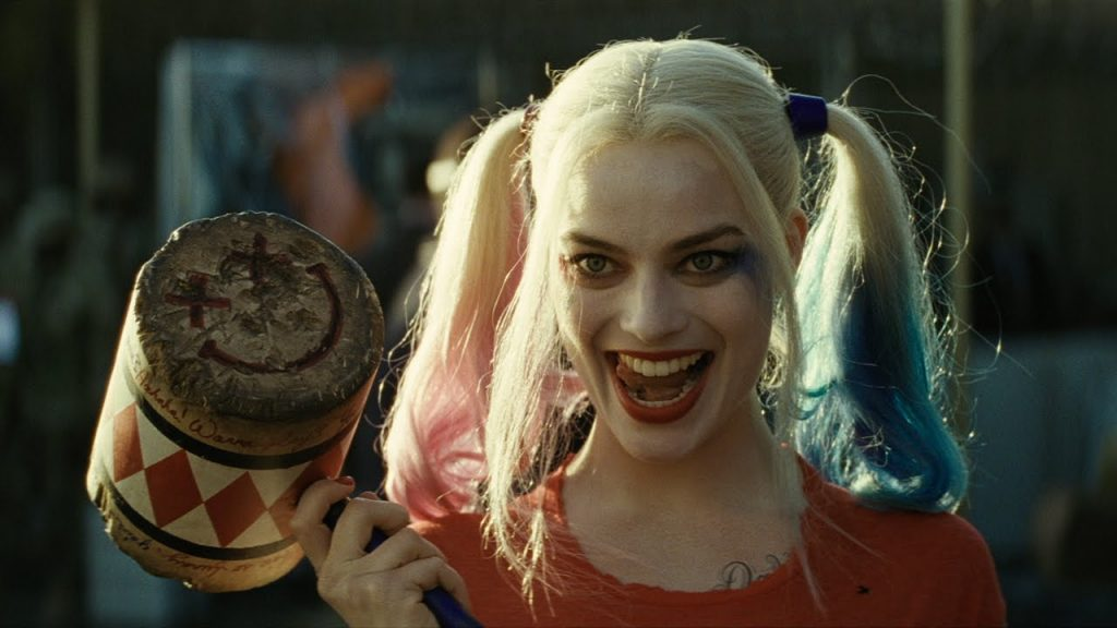 Harley Quinn holding a hammer and looking menacing.