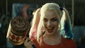 Harley Quinn holding a hammer and looking menacing.