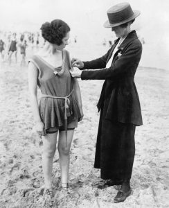 A police officer measuring a woman's bathing costume.