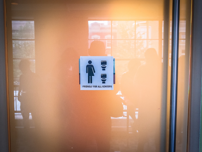 A bathroom sign welcoming all genders.