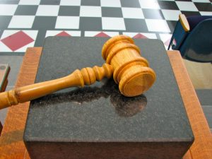 A gavel lying on a block.