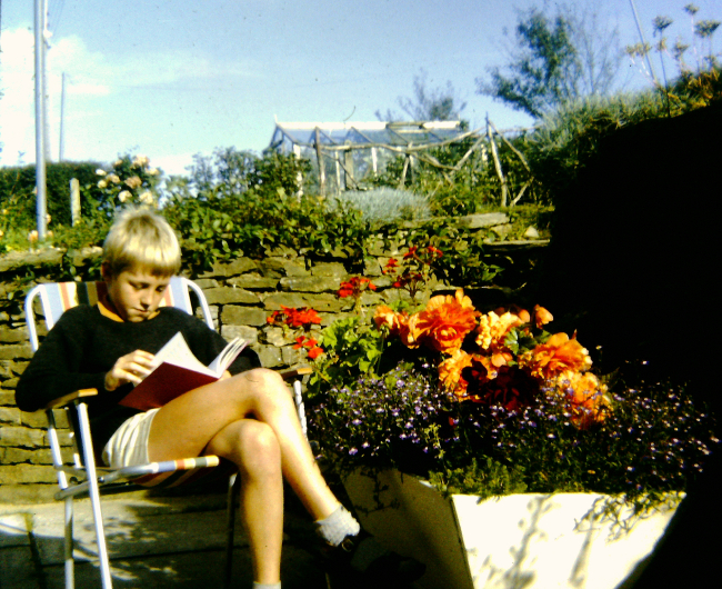 A person lounging in a chair reading outside.