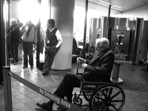 A black and white photo of an old man marooned in a clearly clunky, ill-fitting wheelchair that he would have difficulty propelling on his own at an airport.