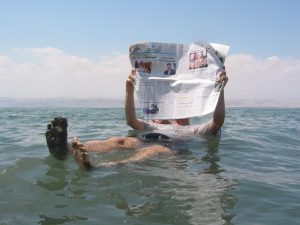 A person floating on the Dead Sea while reading a paper.