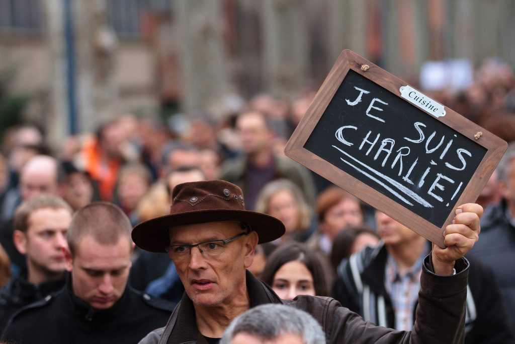A crowd of people at an event commemorating the Charlie Hebdo shooting.