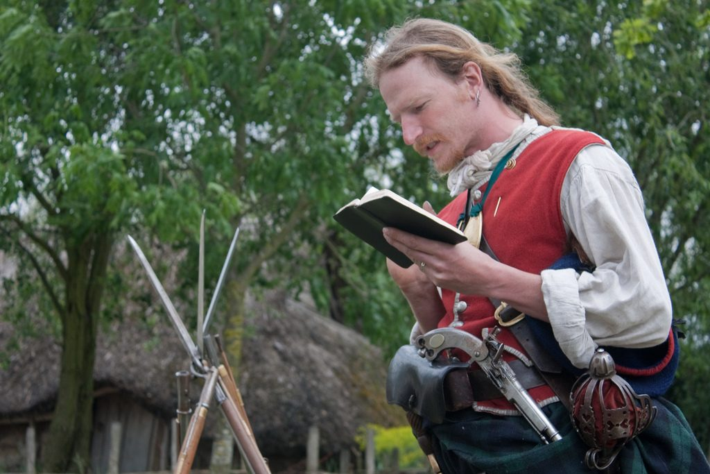 A person in a historical reenactment costume reading a book.