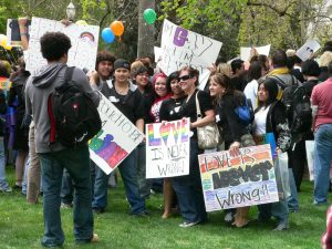 LGBQT youth at gay pride with signs.