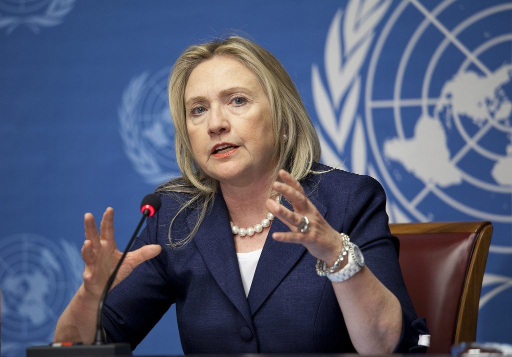 Secretary Clinton speaking at a UN event, gesturing with her hands.