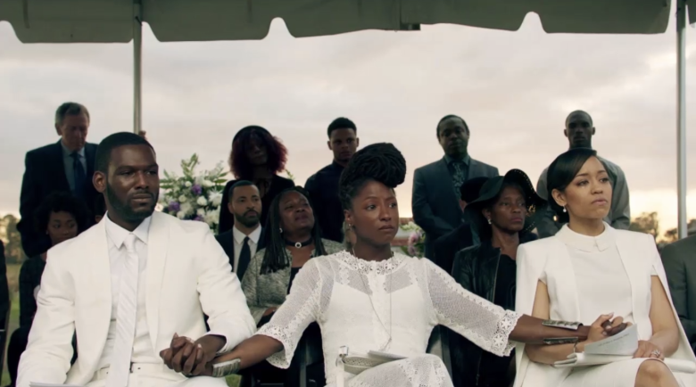 A still from Queen Sugar, showing people sitting at a graveside during a funeral.