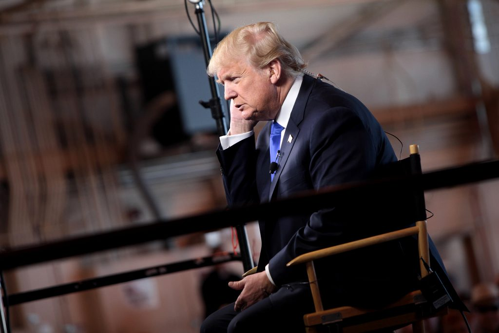 Donald Trump hunched over in a chair preparing for an interview.