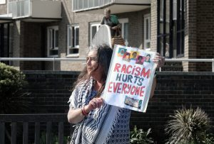 A person holding up a sign that says RACISM HURTS EVERYONE