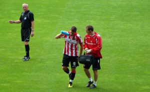 Footballer Ched Evans talking to a field official.