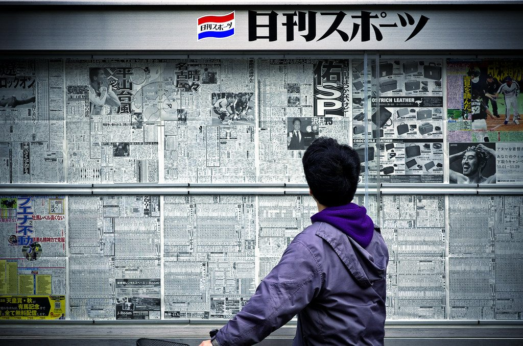 A Japanese person reading newspapers pasted on a wall.