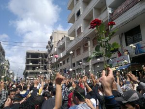 Protesters in Syria in 2011 holding roses as they march down the street.