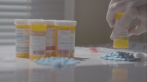A still from Dr. Feelgood showing someone counting out pills.