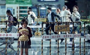 A child standing alone on a train platform in Train to Busan.
